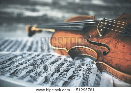 Closeup of vintage violin placed on notes. Aged wooden background