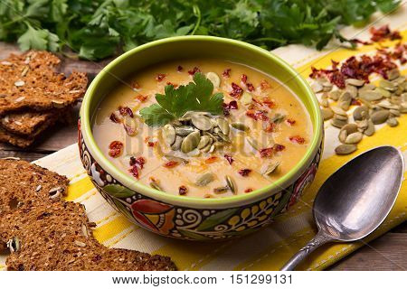 Homemade cream soup from baked butternut squash with thyme and paprika decorated with parsley and with rye crackers with pumpkin seeds and pepper