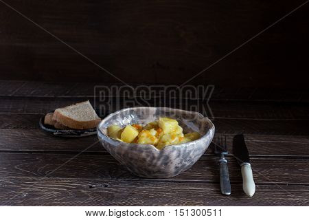 potato stew in a ceramic bowl potato stew on a brown background