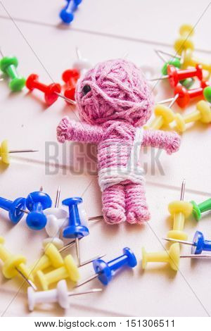 Colourful still life on a pink mummy voodoo doll scattered amongst pins and needles. Halloween black magic