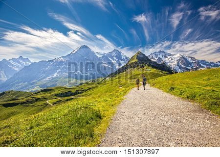 Young couple hiking in panorama trail leading to Kleine Scheidegg from Mannlichen with Eiger Monch and Jungfrau mountain (Swiss Alps) in the background Berner Oberland Grindelwald Switzerland.