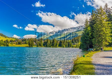 Man Fishing In Heidisee Near Lenzerheide Village With Haidisee, Arose Rothorn And Swiss Alps. Lenzer