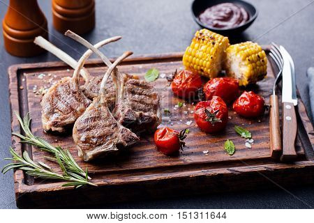 Lamb ribs grilled on cutting board with roasted vegetables. Slate stone background