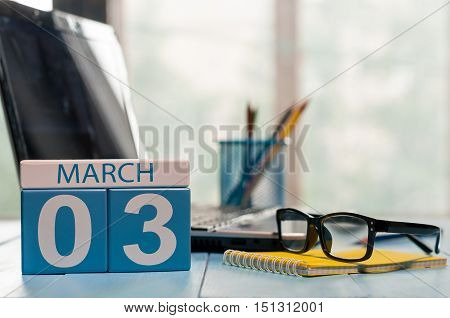 March 3rd. Day 3 of month, calendar on business office background, workplace with laptop and glasses. Spring time, empty space for text.