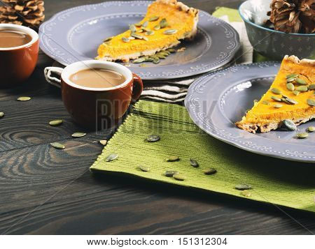 Slice of fall shortcrust pumpkin pie with pumpkin seeds on rustic wooden table with green napkin. Toned image