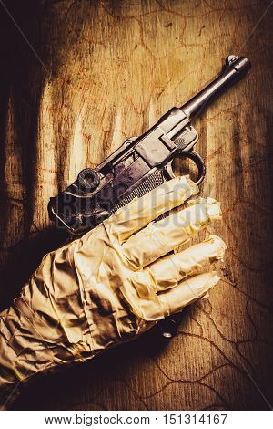 Closeup on a mummy hand holding gun against wooden wall. Curses of revenge