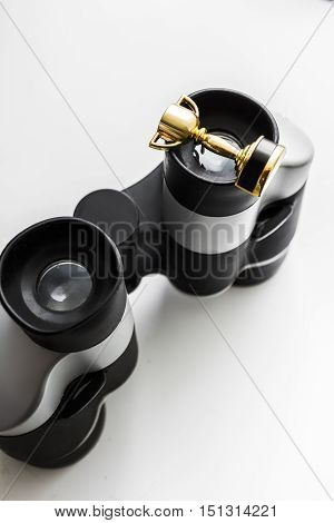 High Angle View of a Tiny Gold Winners Cup Resting on Top of the Eye Piece on a Pair of Binoculars on White Background. Looking to win