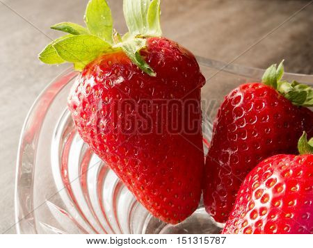 A detail of three red sweet strawberries in a glass transparent bowl