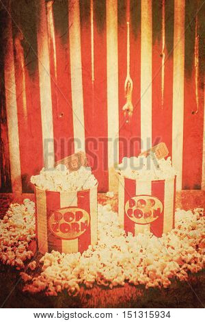 Vintage red striped two old popcorn boxes overflowing with buttered popcorn coupled with movie tickets classical cinema interval concept