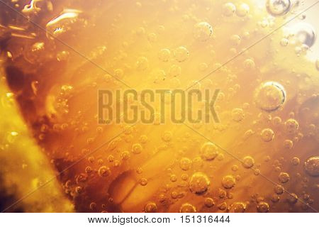 Full frame close up of orange soda water with various sized bubbles and copy space