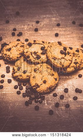 Pile of freshly baked delicious crunchy homemade cookies with choco chips topping on wooden surface