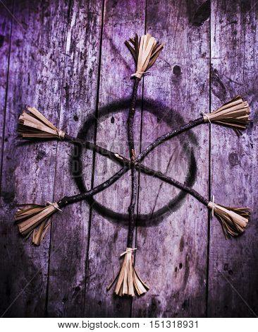 Pagan or witchcraft symbol for a gathering of witches with a magic circle formed of broomsticks to enhance casting of spells. Halloween background