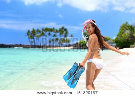 Happy beach vacation girl having fun doing snorkel watersport activity in caribbean ocean. Asian woman enjoying swimming in tropical destination vacation travel holidays on white sand beach.