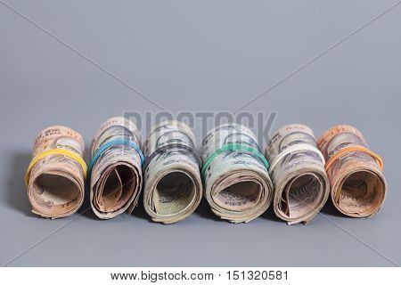 Rolls of Indian rupees isolated on gray background