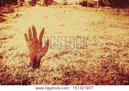Spooky and gruesome bloody hand of a zombie awakening for the apocalypse rising from turf on a moonlit night with copy space for your Halloween message