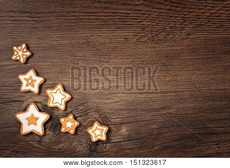 Star shaped gingerbread cookies border over a wooden background