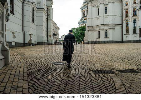 monk crossing himself in the yard of Kyiv Pechersk Lavra, Kyiv, Ukraine