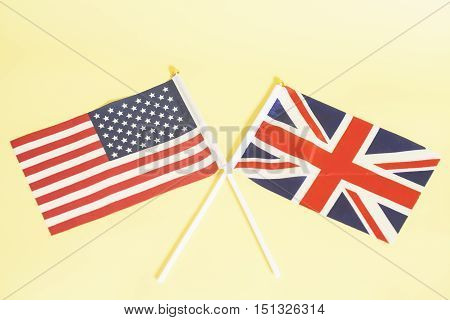 British (UK) and American (USA) flags on yellow background