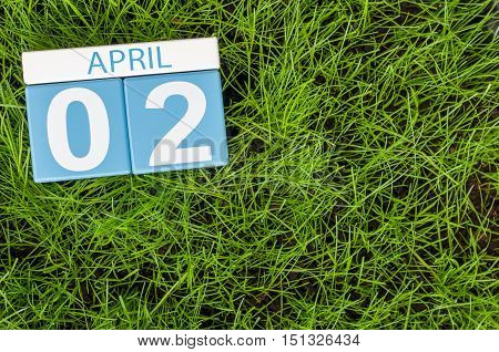 April 2nd. Day 2 of month, calendar on football green grass background. Spring time, empty space for text.