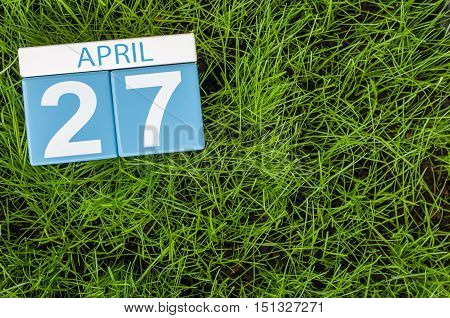 April 27th. Day 27 of month, calendar on football green grass background. Spring time, empty space for text.