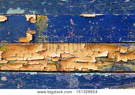 Texture background - old painted wooden surface with peeling blue and orange paint. Colorful texture wooden background