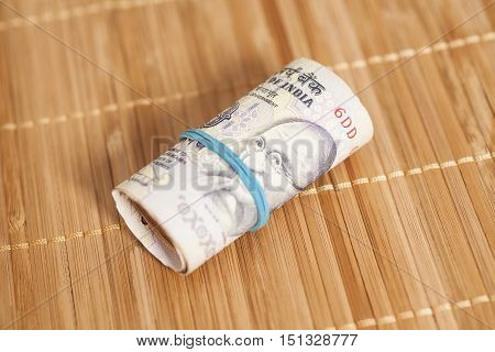 Roll of Indian rupees on wooden background