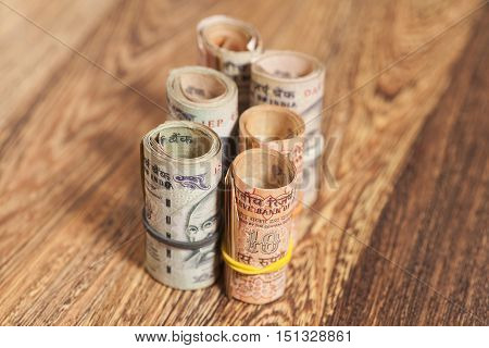 Rolls of Indian rupees on wooden background