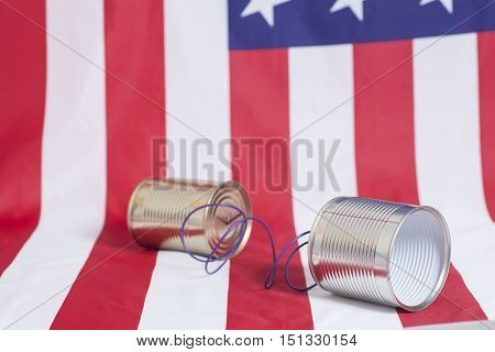 Tin can phone on American flag.Communication concept