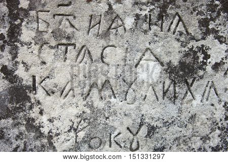 The surface of the old cross gravestone with engraved Old Church Slavonic inscriptions. Kyiv Ukraine. Close up.