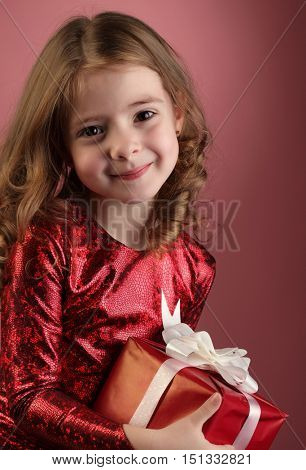 Happy Little girl with red gift box, child holding a gift from Santa Claus with a magic Christmas present