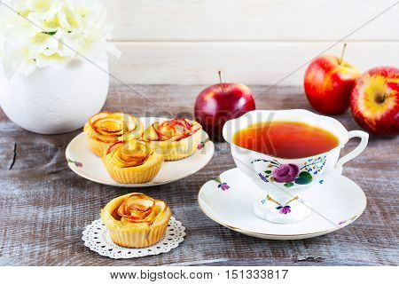 Cup of tea and muffins with rose shaped apple slices. Sweet apple dessert pie. Homemade apple rose pastry. Breakfast tea with sweet apple pastry