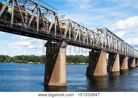 Petrivskiy railroad bridge in Kyiv across the Dnieper with freight train on it.