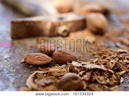 closeup of a pile of shelled almonds and its cracked shells after being open with a hammer, pictured in the background
