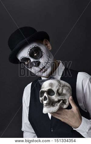 portrait of a young man with a mexican calaveras makeup, wearing waistcoat, bow tie and bowler hat, holding a skull in his hand