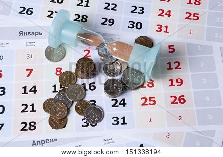 Hourglass on calendar sheets lie near rubles