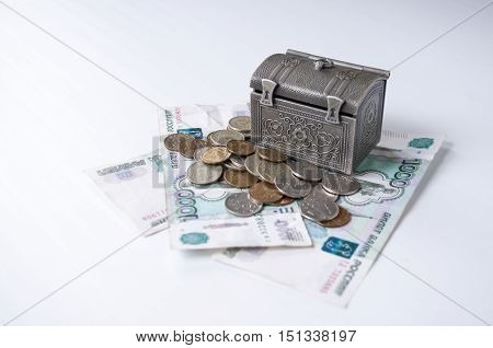Iron chest stands on the banknotes with small coins