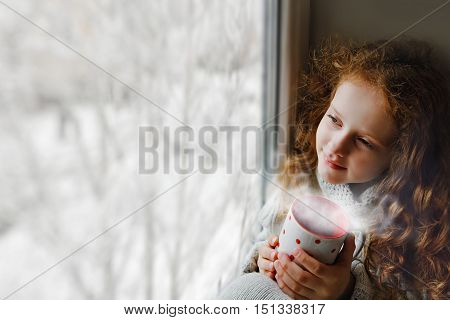 Cute little girl sitting with a cup of hot cocoa by the window and looking on first falling snow through glass early Christmas morning. Toning to instagram filter.