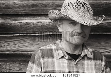 horizontal sepia head shot of a cowboy standing next to an old wood plank wall wearing a cowboy hat and checkered shirt with space for text.