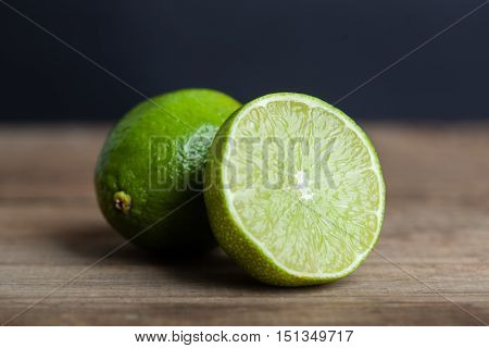 green lime on wooden rustic table in center of frame