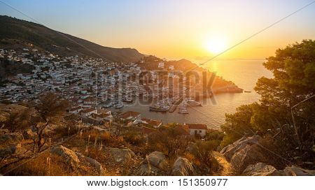 Beautiful sunset of Hydra island, Greece - top view of city center and yaht marina.