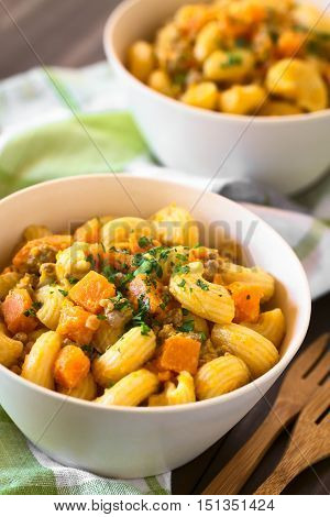 Macaroni pasta with creamy pumpkin and mincemeat sauce garnished with parsley served in white bowls photographed with natural light (Selective Focus Focus in the middle of the first dish)