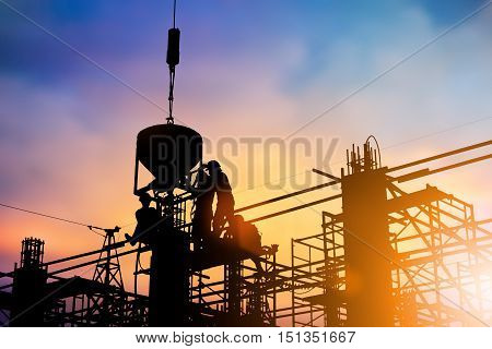 Silhouette of construction workers to work safely on a high with the engineer in charge. construction or planned over blurred pastel background sunset industry. Heavy industry concept.