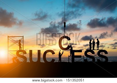 Silhouette's employees work as a team to work out successfully over blurred sky at sunset. Teamwork success Industry Business People engineers working in a systematic concept.