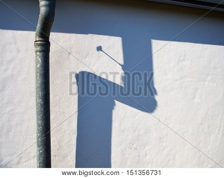 Metal drain pipe against a white wall casting shadow in strong sunlight