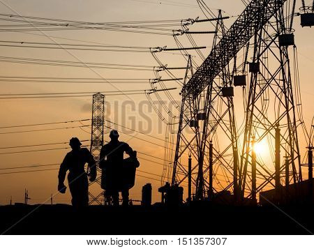 Silhouette of engineer looking at blueprints in a building site over Blurred substation