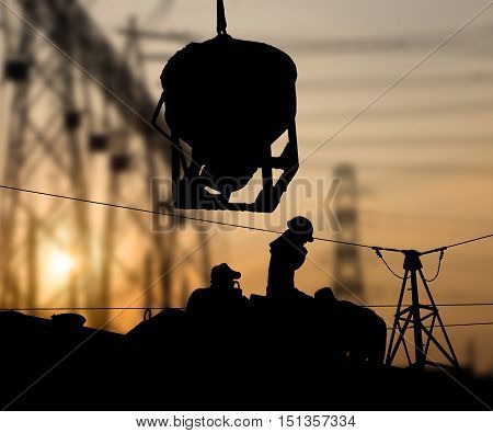 Silhouette working men construction in a building site over Blurred substation