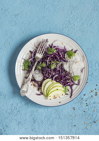 Red cabbage and apple slaw. Vegetarian diet food. On a blue background top view