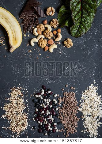 Magnesium rich food - banana chocolate walnuts cashews chard quinoa beans oatmeal lentils. On a dark background top view. Food background