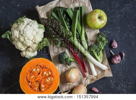 Homegrown harvest - pumpkin cauliflower chard leeks broccoli onion garlic apple. Autumn vegetables. On a dark background top view