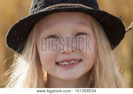 happy little blonde girl in wheat field with long hair, closeup face portrait